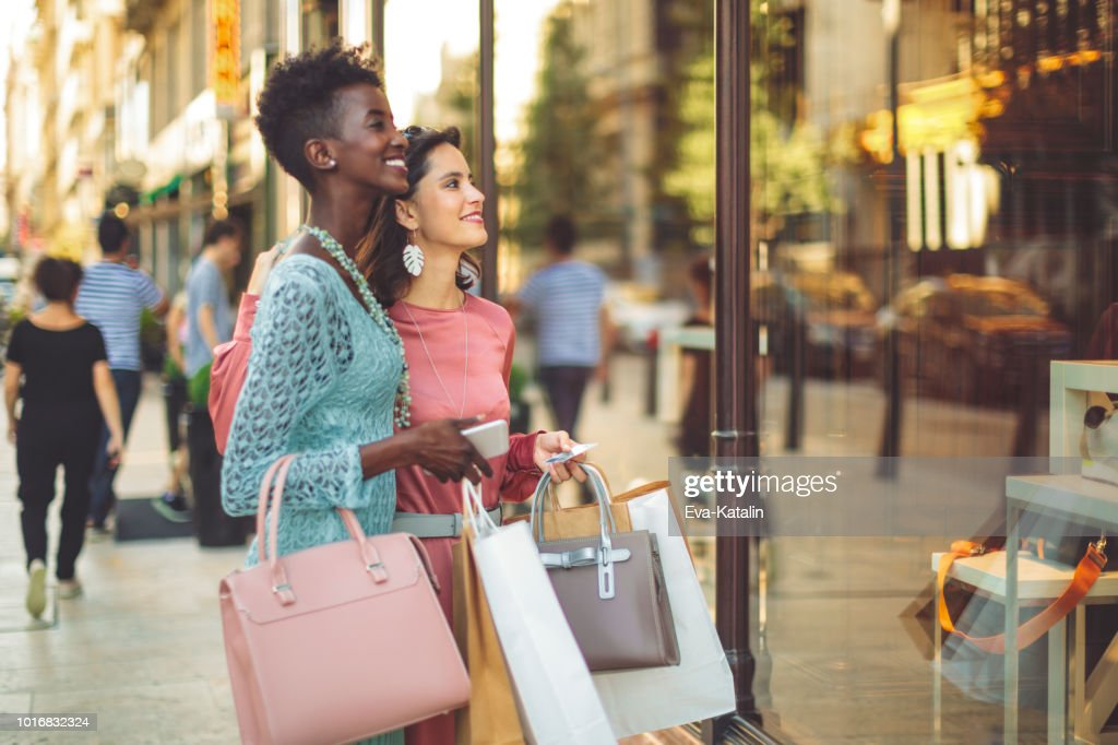 Friends are window shopping in the summer : Stock Photo