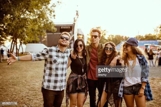 Friends arrived at the music festival, the stage in the background
