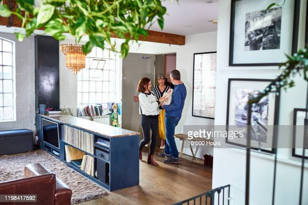 friends arriving at apartment with gift - guest stock pictures, royalty-free photos & images