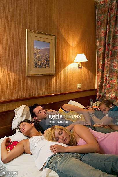 Friends asleep on hotel bed