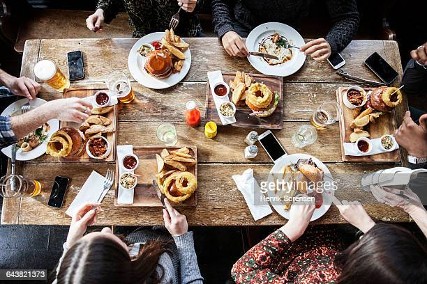 friends at a pub eating, birds view - pub stock pictures, royalty-free photos & images