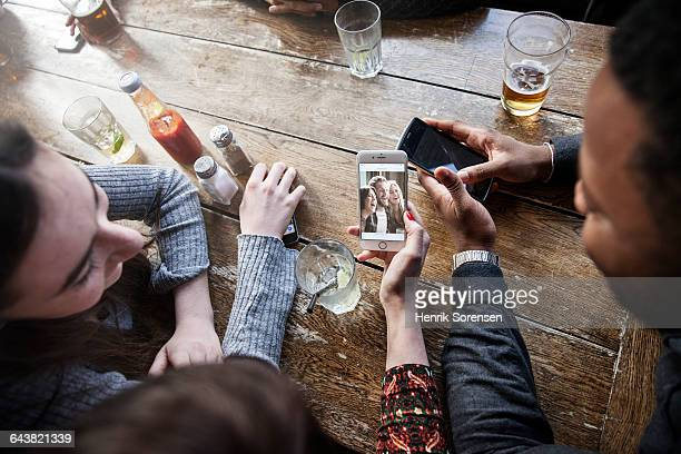 friends at a pub sharing content on phones