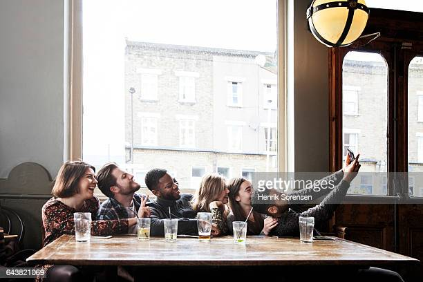 6 friends at a pub taking a group selfie