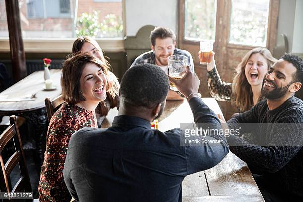 friends at a pub toasting