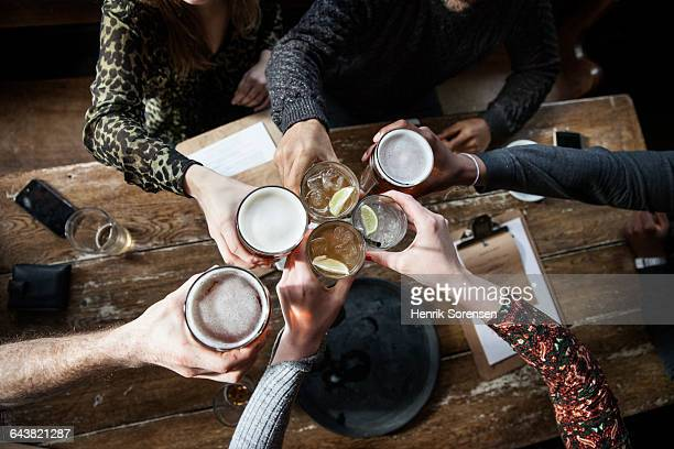 friends at a pub toasting - happy hour stock pictures, royalty-free photos & images