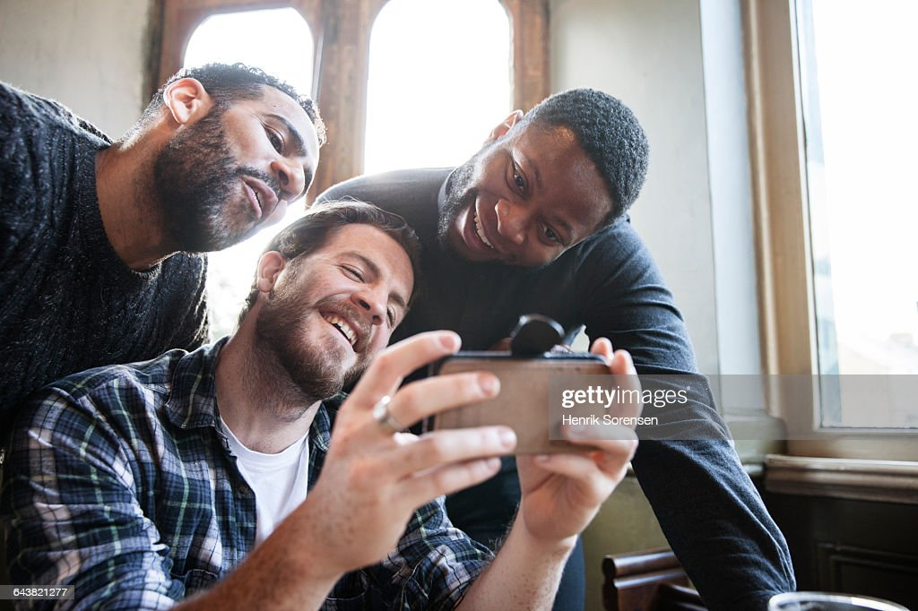 3 friends at a pub, watching video : Stock Photo