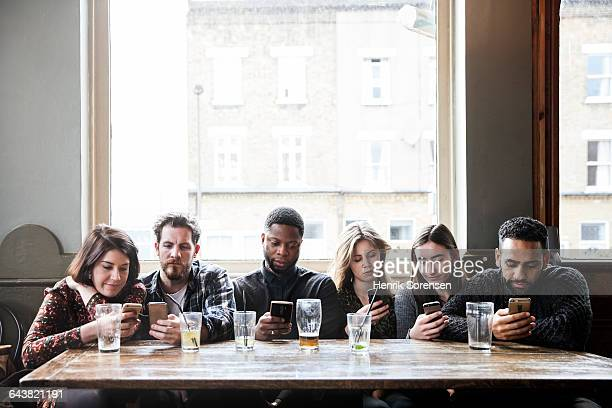 6 friends at a pub with phones - verslaving stockfoto's en -beelden