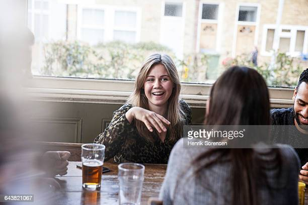 friends at a pub, young woman telling jokes