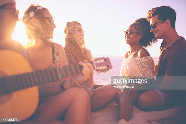 Friends at a sunset beachparty with a guitar