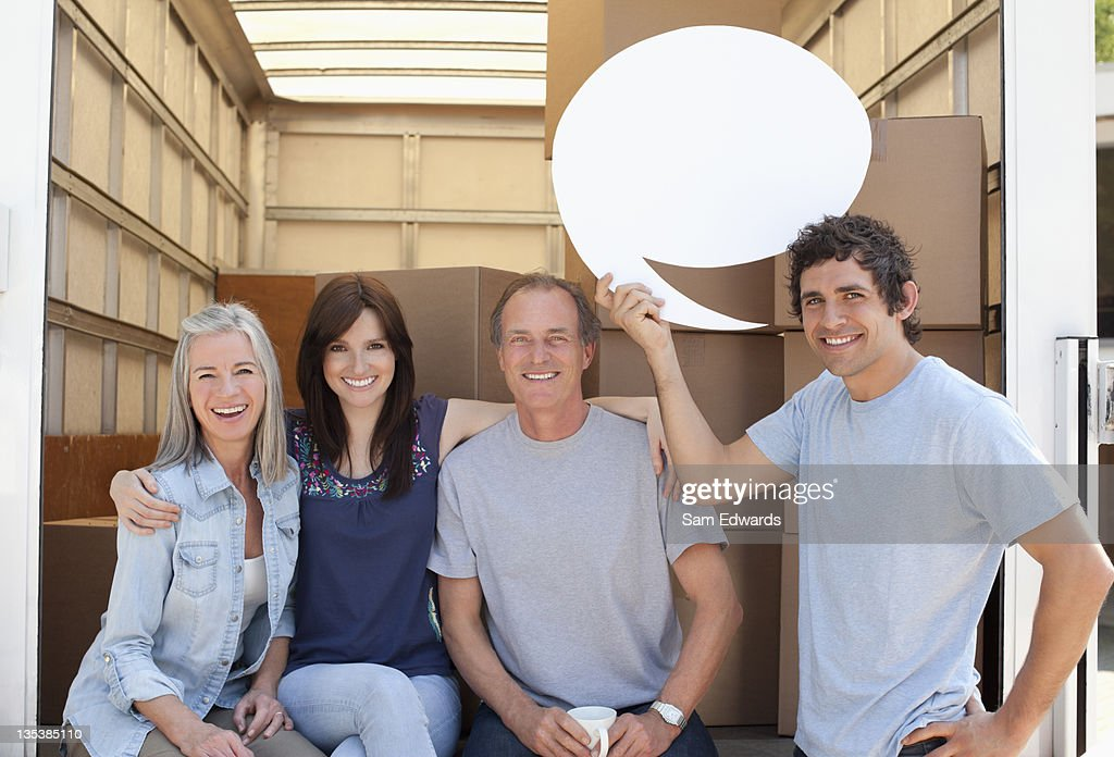 Friends at back of moving van, one holding a comment bubble : Stock Photo