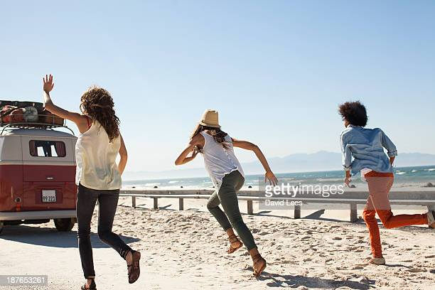 Friends at beach running after camper van