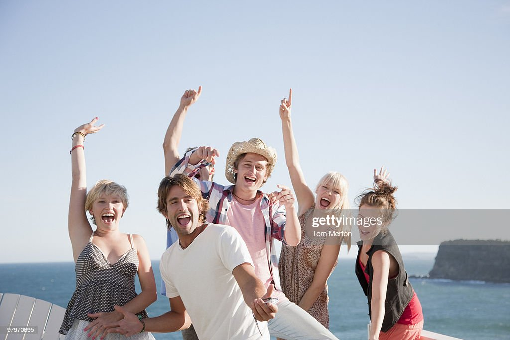 Friends at beach with arms raised : Stock Photo