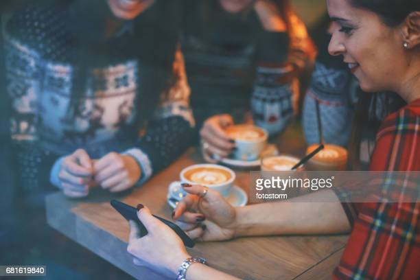 friends at cafe looking down at smartphone - mid section stock photos and pictures
