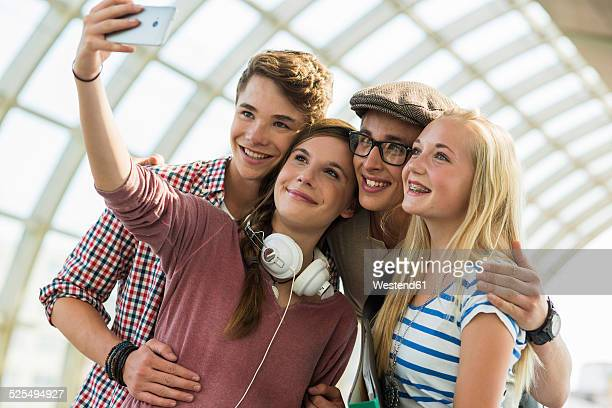 Friends at commuter train station taking a selfie