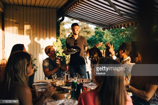 friends at dining table clapping for man serving food in dinner party - middelgrote groep mensen stockfoto's en -beelden