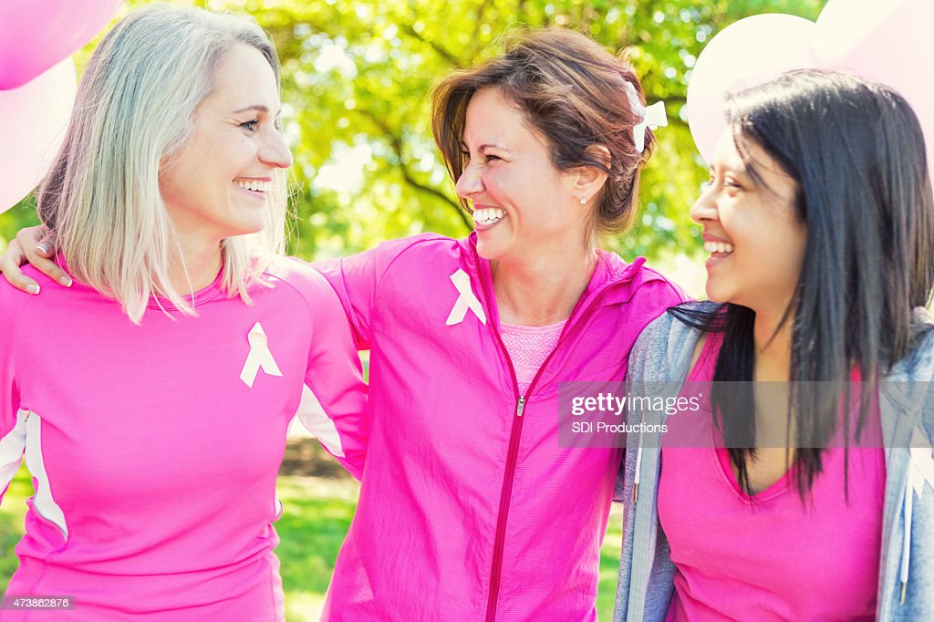 Friends at finish line of breast cancer awareness charity race : Stock Photo