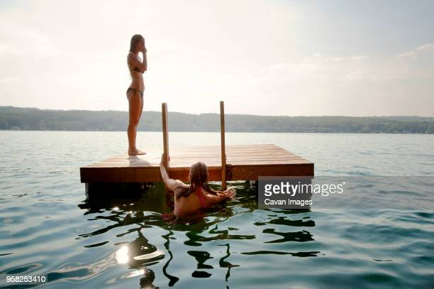 Friends at floating platform in lake against sky on sunny day