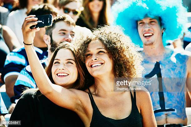 Friends at football game in stadium taking selfie