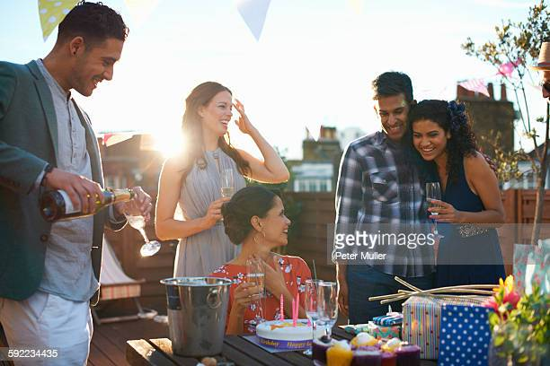 Friends at party on roof terrace pouring champagne