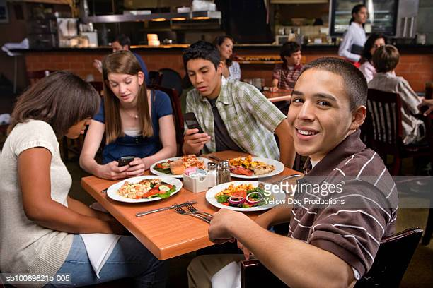 Friends at restaurant table with food looking at mobile phone