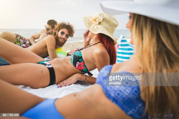 Friends at sea: relaxing on the beach at sunset
