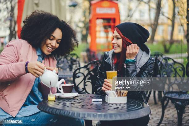 friends at sidewalk cafe drinking coffee - coffee stock pictures, royalty-free photos & images