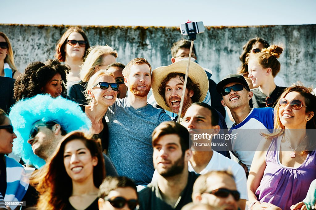 Friends at sporting event using a selfie stick : Stock Photo