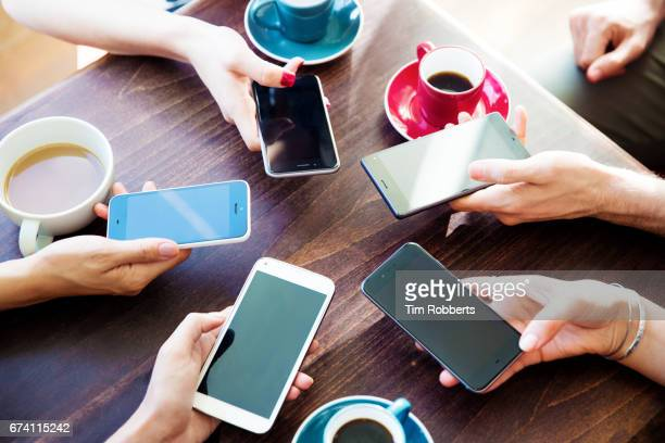 friends at table with circle of smartphones - part of stock pictures, royalty-free photos & images