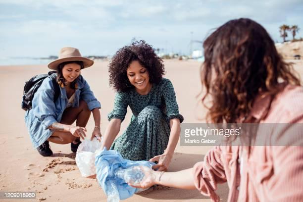 friends at the beach - umweltschutz stock-fotos und bilder