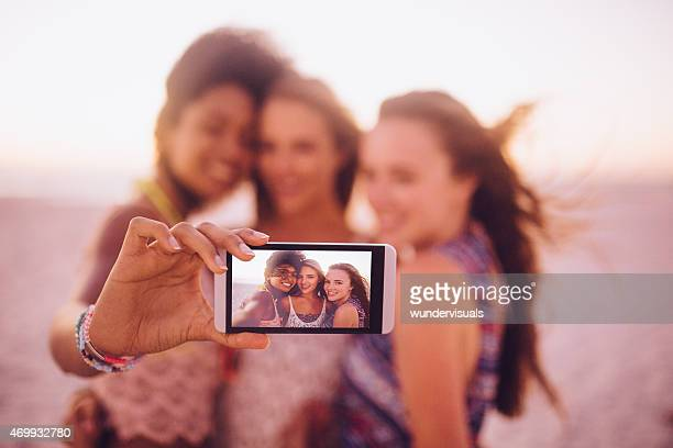 Friends at the beach taking a selfie on their phone