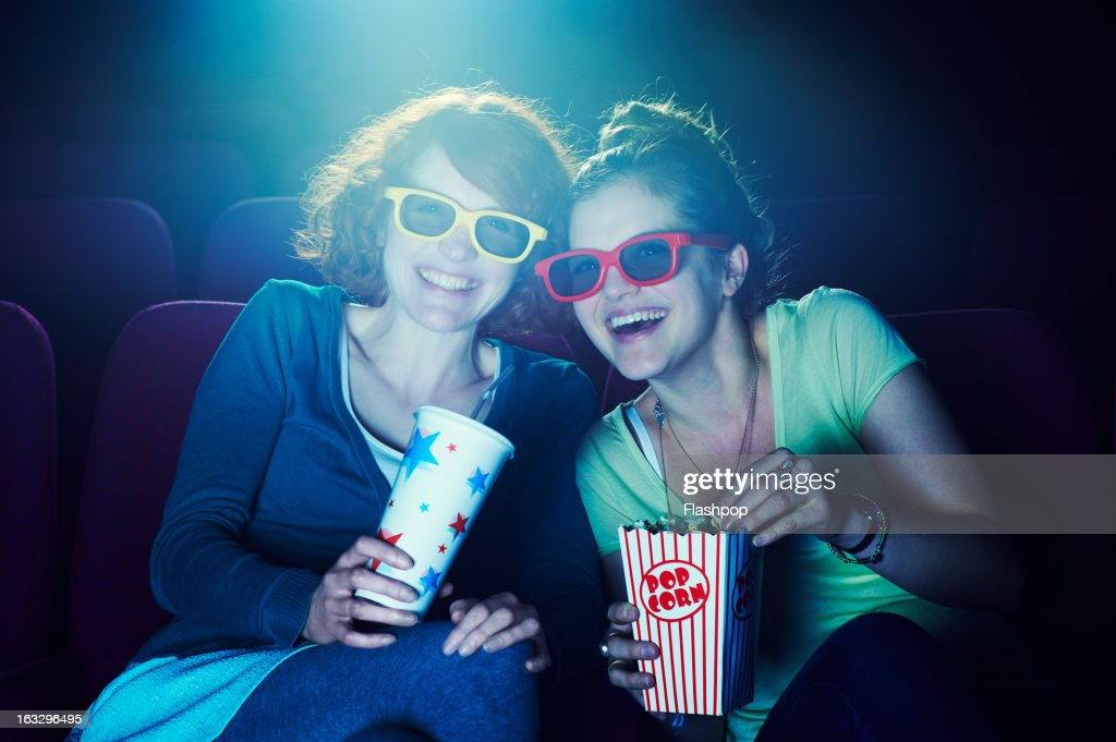 Friends at the cinema wearing 3D glasses : Stock Photo