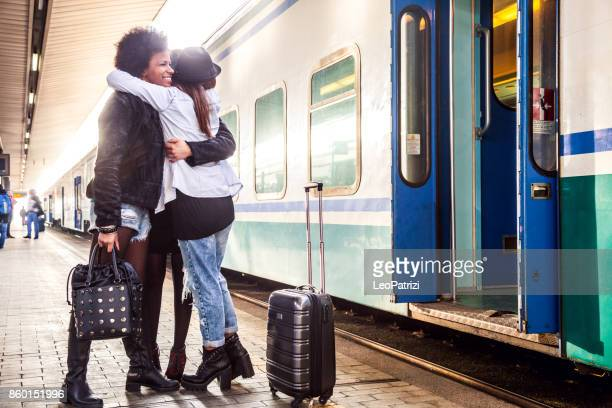Friends at train station platform, tourist and commuters arriving