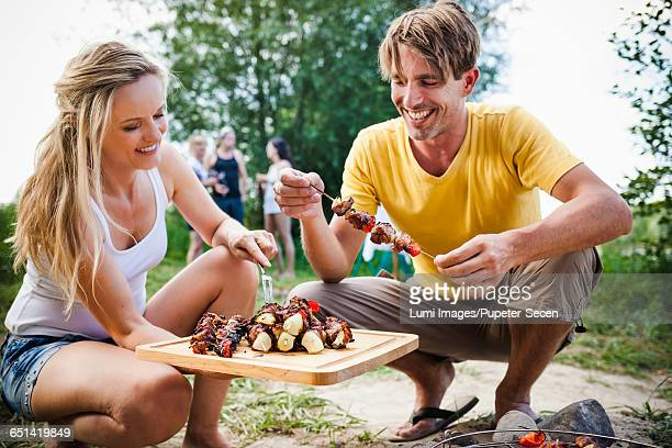 Friends barbecuing on the riverside, foothills of the Alps, Bavaria, Germany