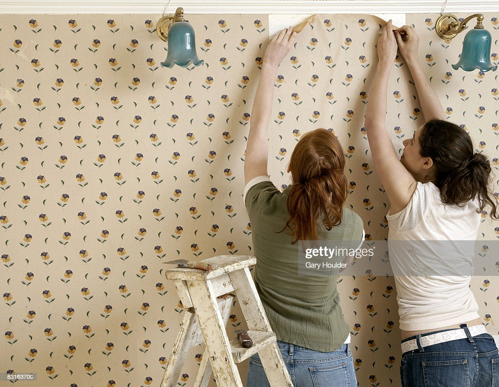 Friends beginning to remove wallpaper : Stock Photo