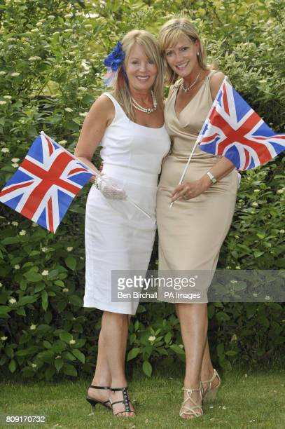 Friends Beverley Britton and Elaine Green from Devon wave flags as they join in with the royal wedding celebrations in the village of Chapel Row near...