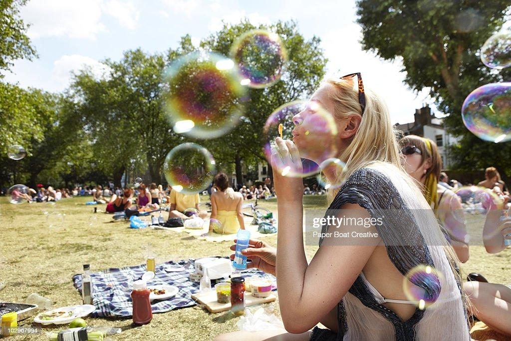 Friends blowing bubbles in the park : Foto de stock
