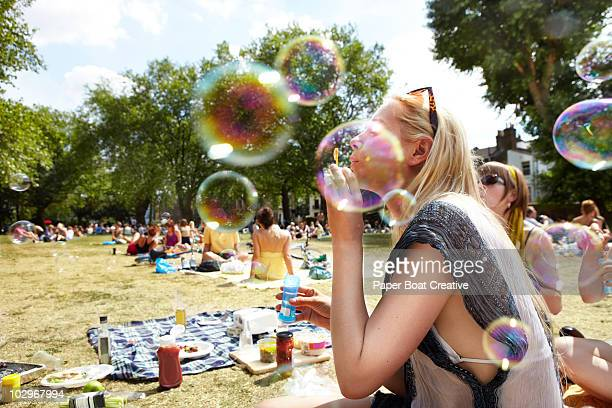 friends blowing bubbles in the park - picknick stock-fotos und bilder