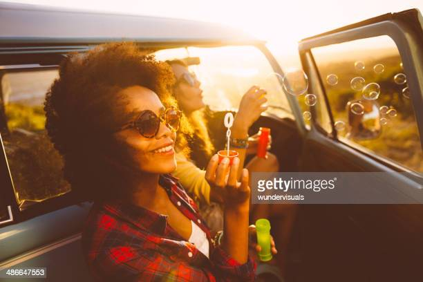 friends blowing bubbles on roadtrip - wonderlust stock pictures, royalty-free photos & images