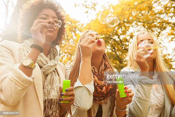 Friends blowing bubbles outdoors