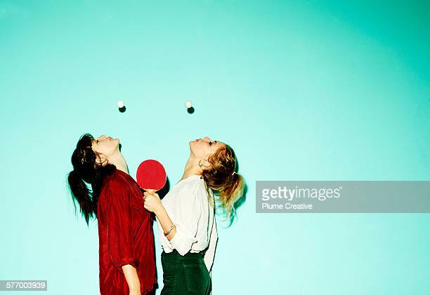 Friends blowing ping-pong balls up.