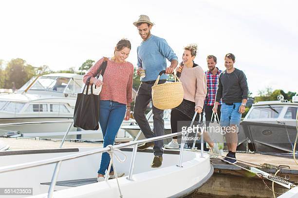 friends boarding yacht against sky - moored stock pictures, royalty-free photos & images