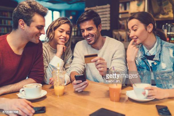 Friends booking trip online with credit card