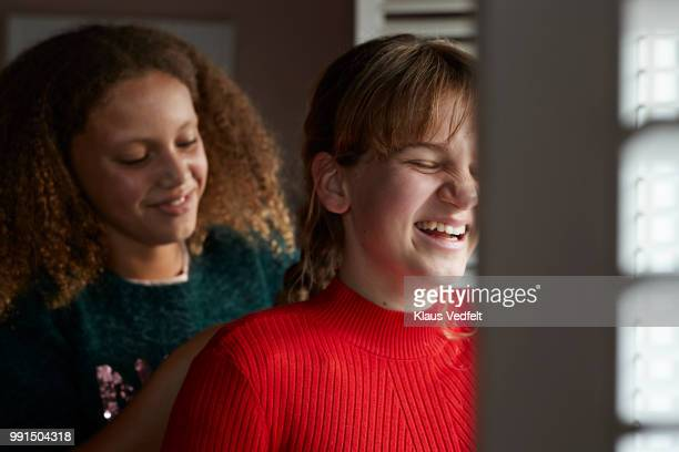 Friends braiding each others hair, at home