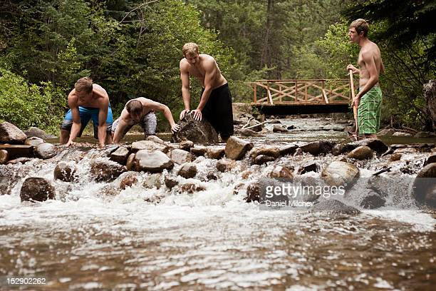 Friends building a river dam.