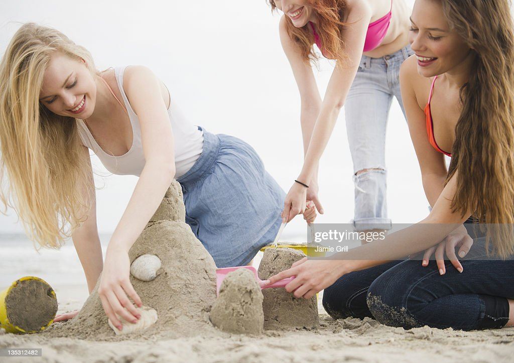 Friends building sandcastle together at beach : Stock Photo