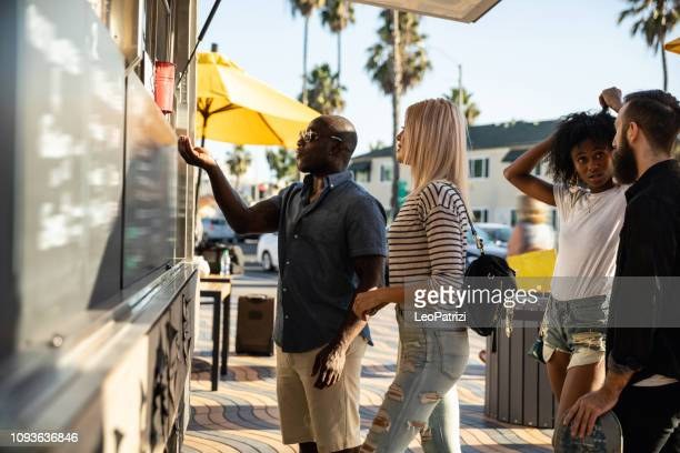 friends buying food in a street food truck - food truck stock pictures, royalty-free photos & images