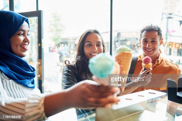 friends buying ice cream in ice cream parlour - ice cream parlour stock pictures, royalty-free photos & images