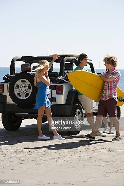 Friends by vehicle with surfboard