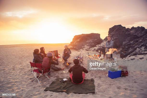 friends camping at beach during sunset - bonfire stock photos and pictures