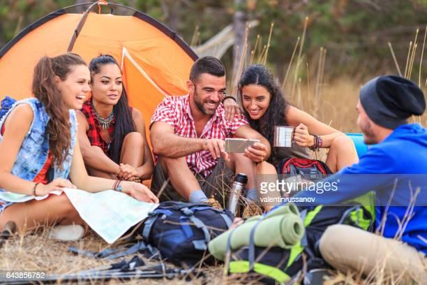Freunde, camping in der Natur und mit Smartphone